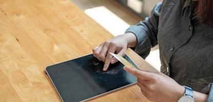 kvinnahandinnehavkreditkort med att använda bärbara datorn för online-shopping medan du gör beställningar hemma. affärs-, livsstils-, teknik-, e-handel-, digitalbank- och onlinebetalningskoncept. foto
