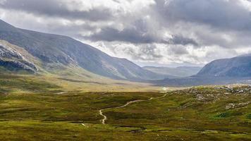 naturskön väg som passerar genom en bergdal foto