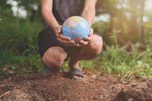 världens miljödag .älskar världen .hand håller en jordglob foto