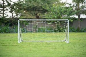 selektivt fokus på ett litet fotbollsmål med repnät sätter på gräsplanen med suddig trädgård och träd i bakgrunden foto