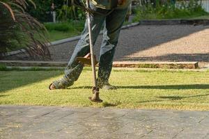 trädgårdsmästare som klipper gräsplanen foto