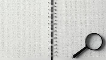 ovanifrån förstoringsglas på punktskrift anteckningsbok foto