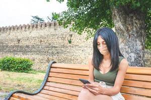 kvinna i en mask som sitter på en parkbänk foto