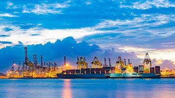 lastfartyg som laddar last vid lastningsdockan vid skymningstid. singapore, sydostasien. foto