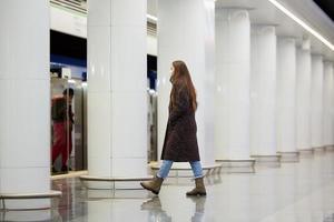 en flicka i en kirurgisk ansiktsmask håller socialt avstånd på en tunnelbanestation foto