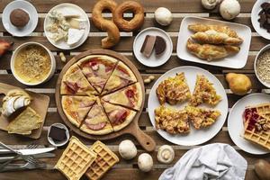 bord fullt av mat platt låg med pizza, våfflor och bröd foto