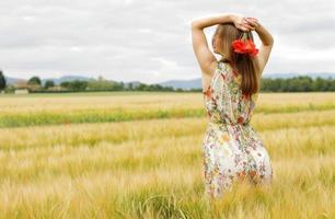 kvinna i en blommig klänning med blommor i ett fält foto
