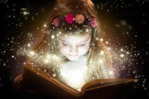 söt liten flicka som läser magisk bok foto