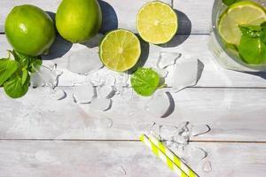 mojito och limefrukter på den vita träbakgrunden foto
