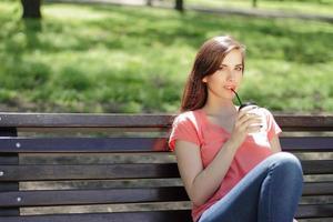 kvinna som dricker kaffe på en parkbänk foto