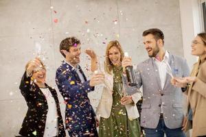 grupp firar och skålar med konfetti foto