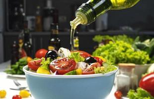 hälla olivolja på färsk grönsaksallad foto