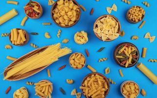 olika pastatyper på blå bakgrund ovanifrån foto