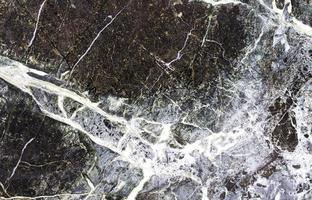 svart sten bakgrund med sprickor svart marmor foto