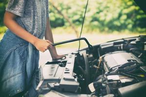 kvinna som reparerar en bil foto