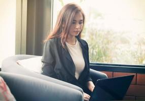 asiatisk affärskvinna som använder bärbara datorn foto