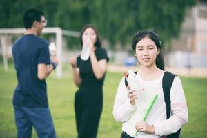 asiatisk student som håller vatten på campus foto