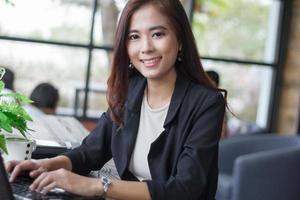asiatiska affärskvinnor som använder bärbar dator i café foto