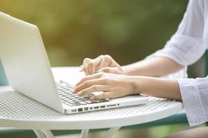 händer som använder bärbar dator för att arbeta utomhus foto