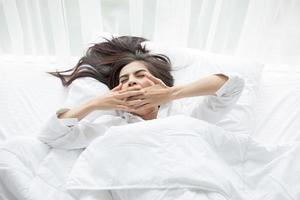 kvinna som gäspar i vit säng foto