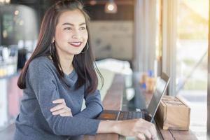 kvinna som ler medan du använder bärbar dator foto