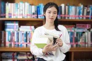 asiatisk student som håller böcker i biblioteket foto