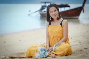 porträtt av en söt flicka som sitter på stranden med en suddig traditionell långsvansbåt i bakgrunden foto