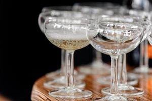 mousserande champagne i glas på träbordet på svart bakgrund foto