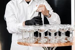 servitören öppnar en flaska champagne foto