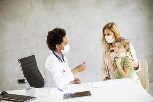 barnläkare som pratar med förälder och barn foto