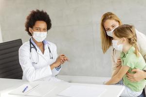 läkare som pratar med barn och förälder foto