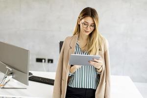 affärskvinna som använder en minnestavla i ett modernt kontor foto