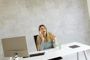 glad affärskvinna på telefon vid skrivbordet foto