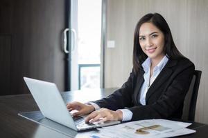 asiatisk affärskvinna som använder en bärbar dator på ett kontor foto