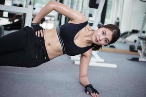 fit kvinna gör sidoplanke i gymmet foto