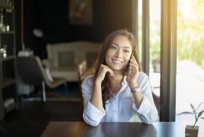 asiatisk kvinna som talar i telefon foto