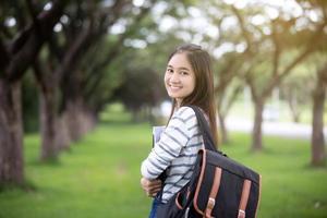 ung asiatisk student som bär ryggsäck foto