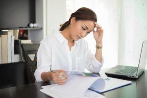 kvinna som läser vid ett skrivbord foto