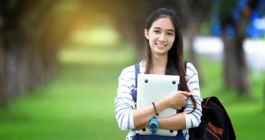 leende studentinnehav bärbar dator foto
