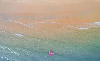 Flygfoto ovanifrån från drönare syn på pojke med simring i havet och skugga smaragdblått vatten och vågskum vid soluppgången foto
