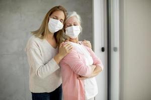 mogen mor och dotter som omfamnar med masker på foto