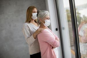 mogen mor och dotter som tittar ut genom fönstret med masker på foto
