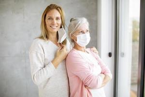 dotter med äldre mamma som tar av sig masken foto