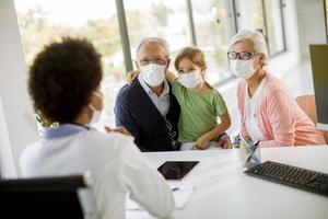 läkare som pratar med farföräldrar och barn foto