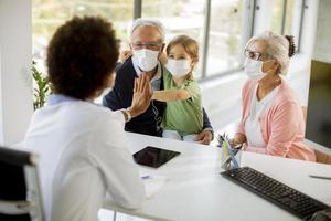 läkare som pratar med farföräldrar och barnbarn foto