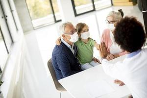farföräldrar och barnbarn som pratar med en läkare foto