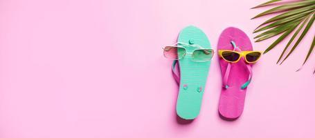sommarhatt med flip-flop på rosa bakgrund foto