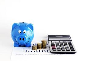 blå spargris och miniräknare med pengar mynt för lån koncept foto