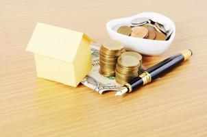 huspapper och reservoarpenna med pengarmynt stack på trä skrivbord bakgrund foto