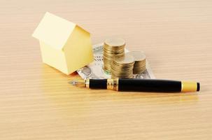 huspapper med pengarmyntstapel och reservoarpenna för lånepengekoncept foto